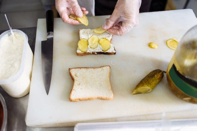 повар в пластиковых перчатках делая сэндвич на белой доске стоковые изображения