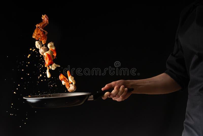 Повар подготавливает части бекона с чесноком и горячим перцем в лотке, замораживанием в воздухе, на черной предпосылке, рецепт-кн стоковое фото