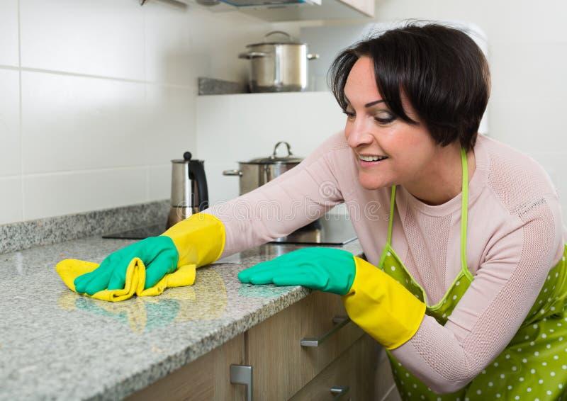 Поверхности кухни положительной домохозяйки полируя стоковое изображение