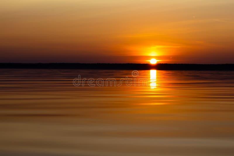 Поверхность воды Взгляд предпосылки неба захода солнца Драматическое небо захода солнца золота с облаками неба вечера над морем В стоковое фото rf
