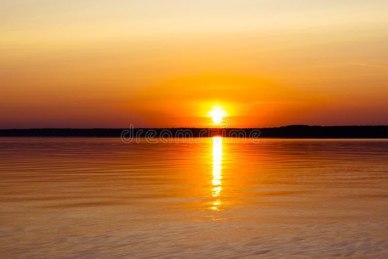 Поверхность воды Взгляд предпосылки неба захода солнца Драматическое небо захода солнца золота с облаками неба вечера над морем В стоковые изображения rf