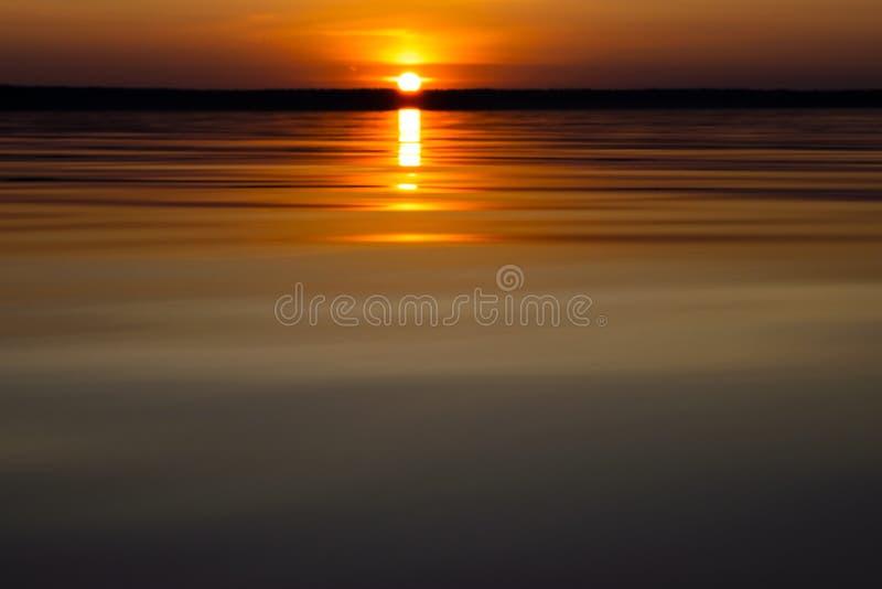 Поверхность воды Взгляд предпосылки неба захода солнца Драматическое небо захода солнца золота с облаками неба вечера над морем В стоковые фото