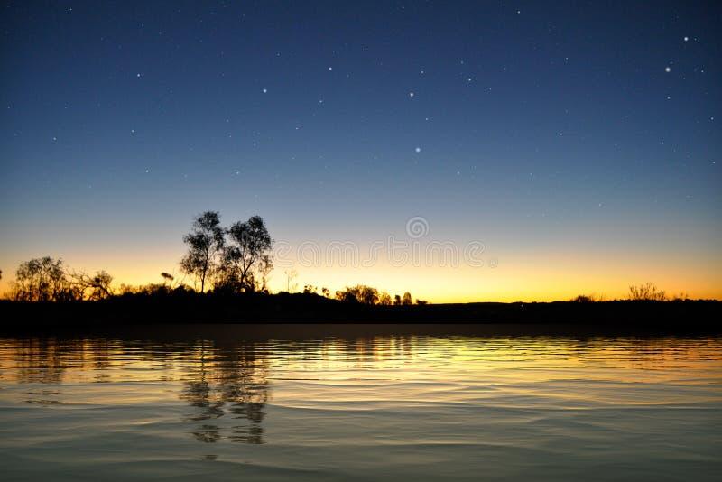 Поверхность озера после захода солнца с звездами стоковое изображение