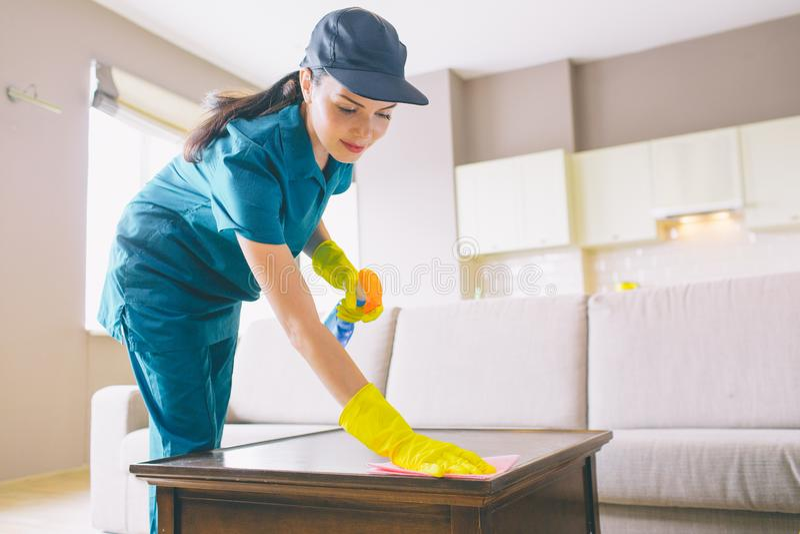 Поверхность профессионального уборщика wahsing таблицы она использует ветошь и брызг Девушка делает ее тщательную стоковые фотографии rf