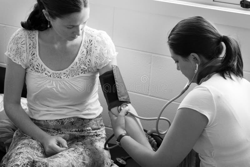 Повитуха проверяет кровяное давление беременной женщины стоковая фотография