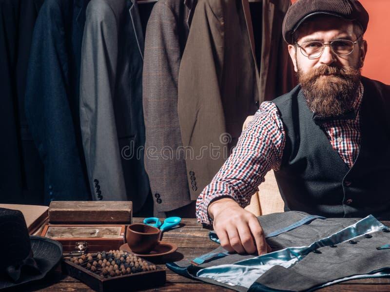 Поворачивая идеи в одежду Его дизайны в требовании Куртка бородатого портноя человека шить магазин костюма платье дела стоковые изображения