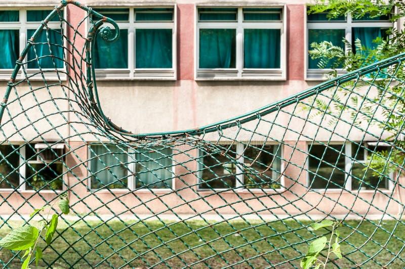 Поврежденная зеленая сломанная проволочная изгородь металла передернутая и стоковая фотография