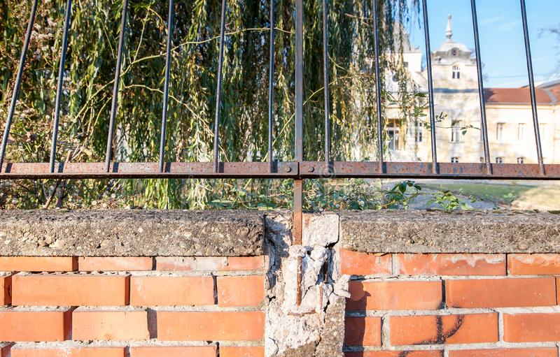 Поврежденная и сломленная красная кирпичная стена с загородкой утюга grunge ржавой стоковая фотография rf