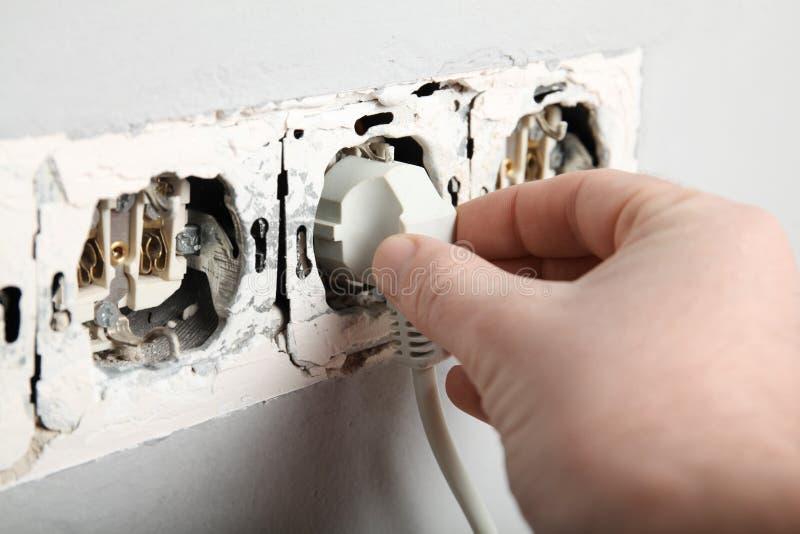 Поврежденное гнездо в стене, опасное электричество в доме стоковые изображения