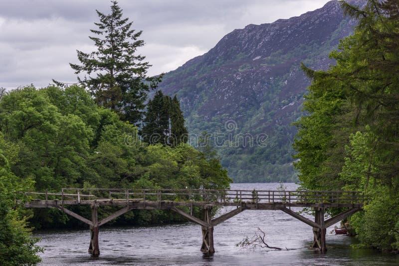 Поврежденный деревянный пешеходный мост над рекой Oich, фортом Augustus Scotla стоковая фотография rf