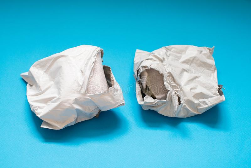 Поврежденный конверт полиэтилена на голубой предпосылке Пластиковые почтовые пересылая сумки стоковая фотография rf