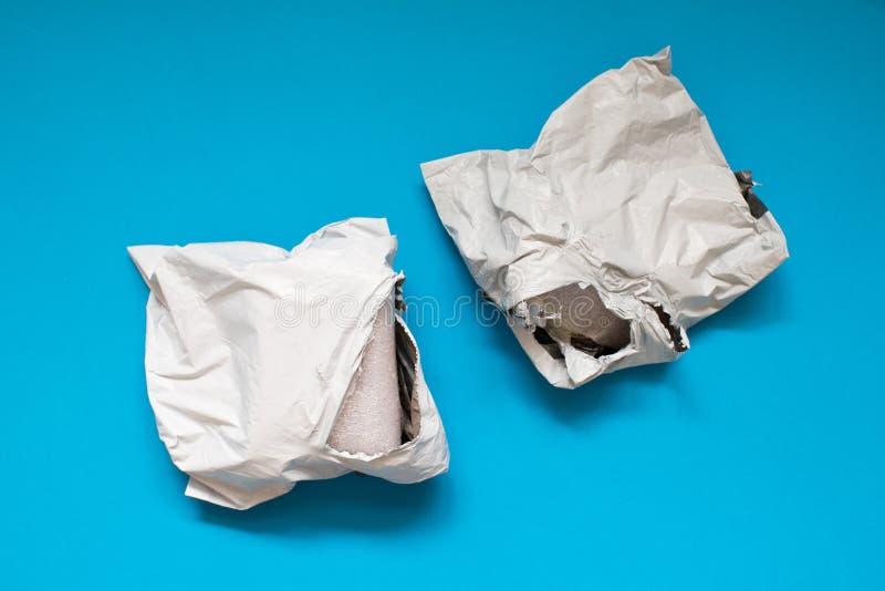 Поврежденный конверт полиэтилена на голубой предпосылке Пластиковые почтовые пересылая сумки стоковые изображения rf