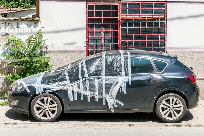 Поврежденный новый черный хэтчбек Opel Astra j припаркованный на улице покрытой и защищенной с нейлоном над сломленным windscreen стоковое фото