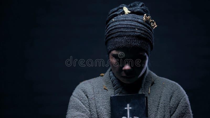 Повреженная бездомная держа библия, молящ для помощи, надеющся на лучшая жизнь, вера стоковое изображение rf
