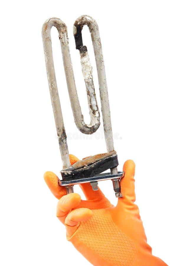 Поврежденный нагревающий элемент стиральной машины в руке с rubb стоковая фотография rf
