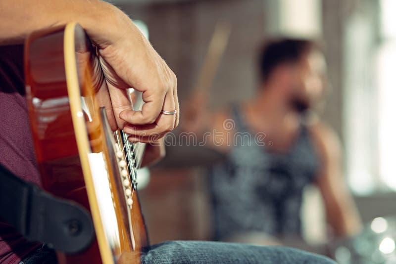 Повторение диапазона рок-музыки Электрические гитарист и барабанщик за комплектом барабанчика стоковое изображение