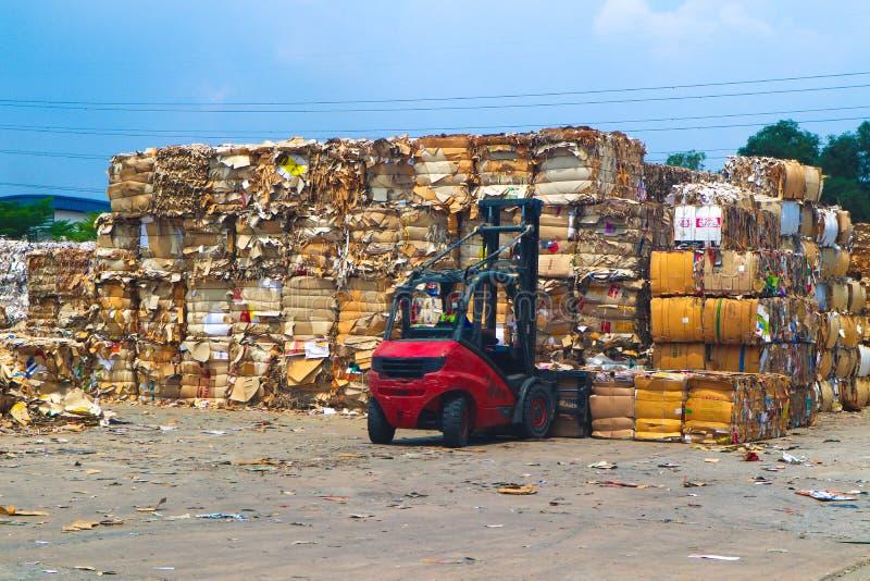Повторно используйте отход отброса и бумаги картона индустрии после отжимать в гидравлической тюкуя машине прессы отброса к квадр стоковые изображения rf