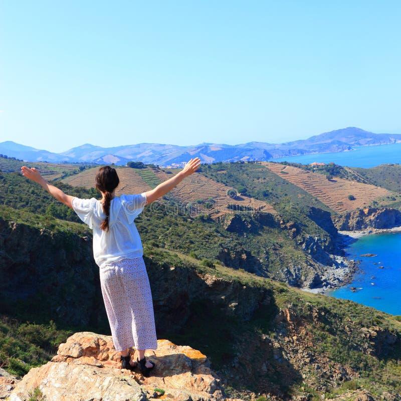 Повышение молодой женщины одно ее оружия к небу перед Средиземным морем, Францией стоковые изображения rf