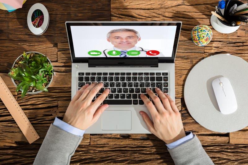 Повышенный взгляд видео конференц-связь предпринимателя с доктором стоковые изображения
