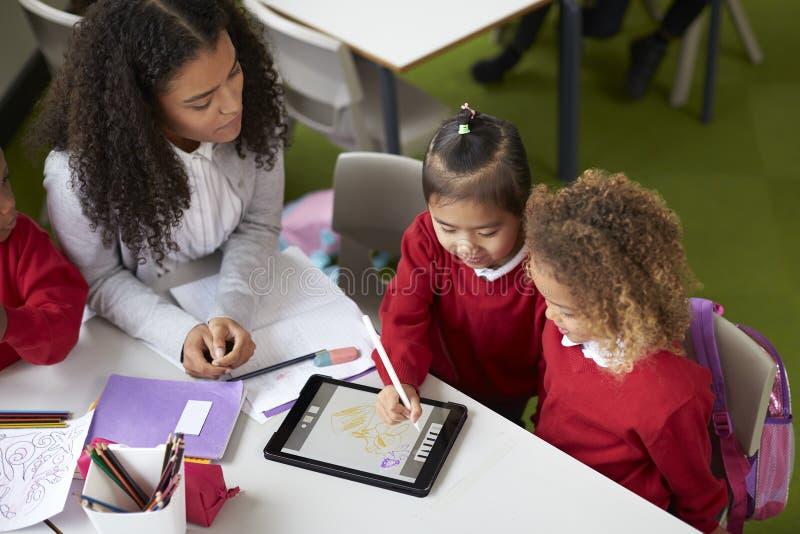 Повышенный взгляд 2 девушек используя планшет сидя на таблице в младенческом школьном классе a с учительницей помогая им стоковые фото