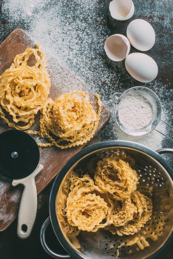 повышенный взгляд регулируемого резца теста, сырцовых макаронных изделий, дуршлага, сетки, раковин яичка и яичек на покрытой табл стоковые фото
