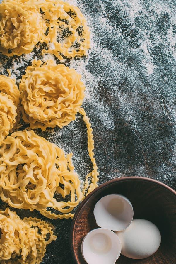повышенный взгляд сырцовых макаронных изделий, шара с яичком и раковины яичка на покрытой таблице стоковое изображение rf