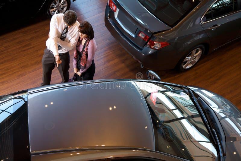Повышенный взгляд продавца автомобилей объясняя характеристики автомобиля к клиенту стоковое фото