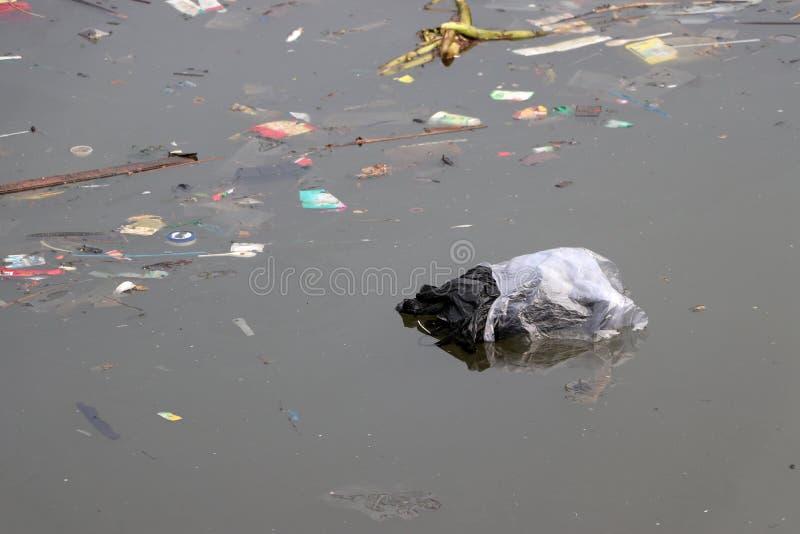 Погань и отброс плавая на поверхность воды, причиняя нечистоты стоковые фото