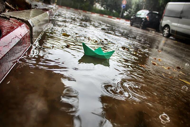 Погода зимы в Израиле Бумажные ветрила шлюпки в лужице во время дождя стоковые изображения
