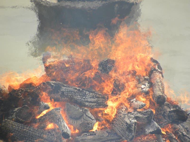 Погребальный костер с древесиной и пламенами огня на землях кремации стоковые фото