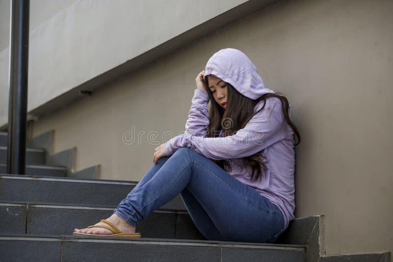 Подавленная азиатская китайская женщина студента или задранная девушка подростка сидя outdoors на жертве лестницы улицы задирая ч стоковые изображения rf