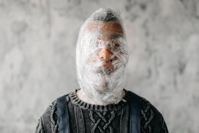 Подавленная аутистическая голова обручей в упаковывая фильме стоковое фото rf