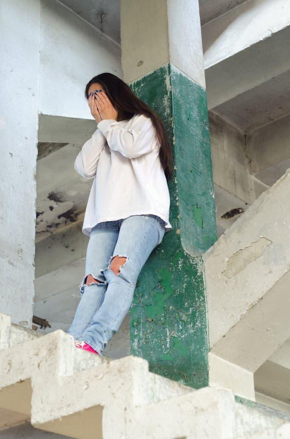 Подавленная женщина плача в покинутом здании стоковое фото rf