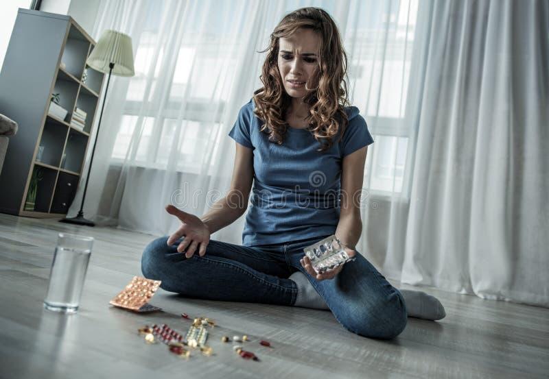 Подавленная молодая женщина принимая вредное лекарство стоковое фото