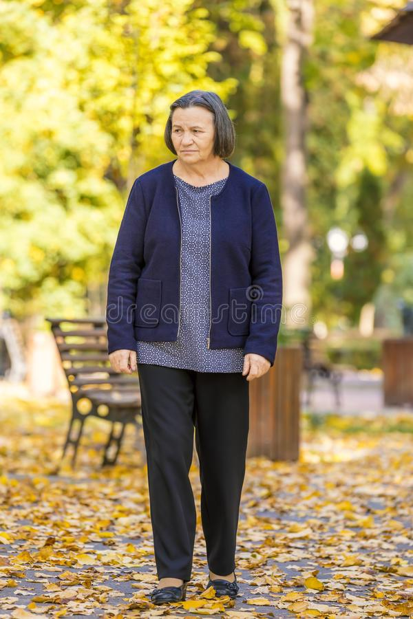 Подавленная старшая женщина идя outdoors стоковая фотография