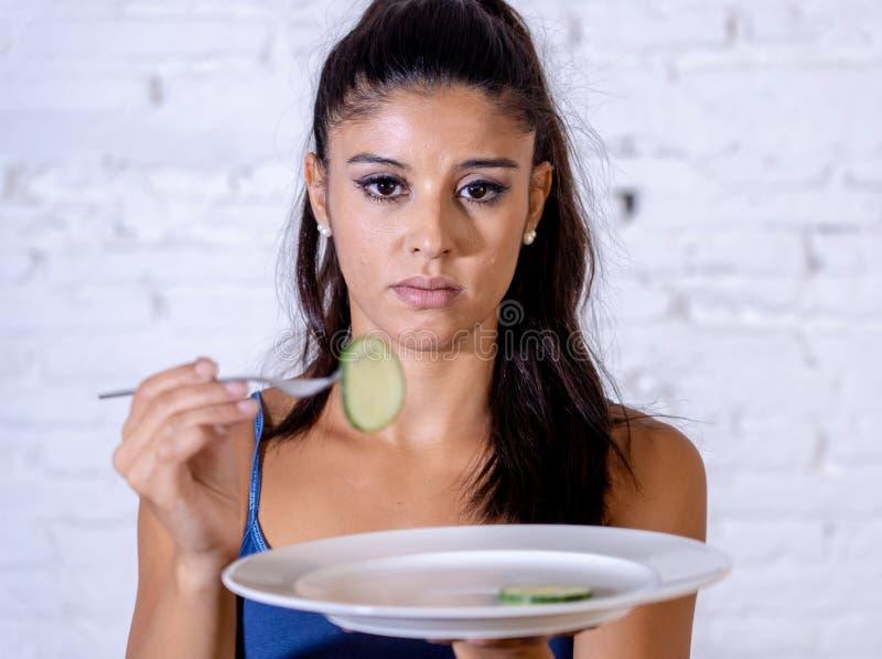 Подавленная dieting женщина держа людей смотря малый зеленый овощ на пустой плите стоковые фотографии rf