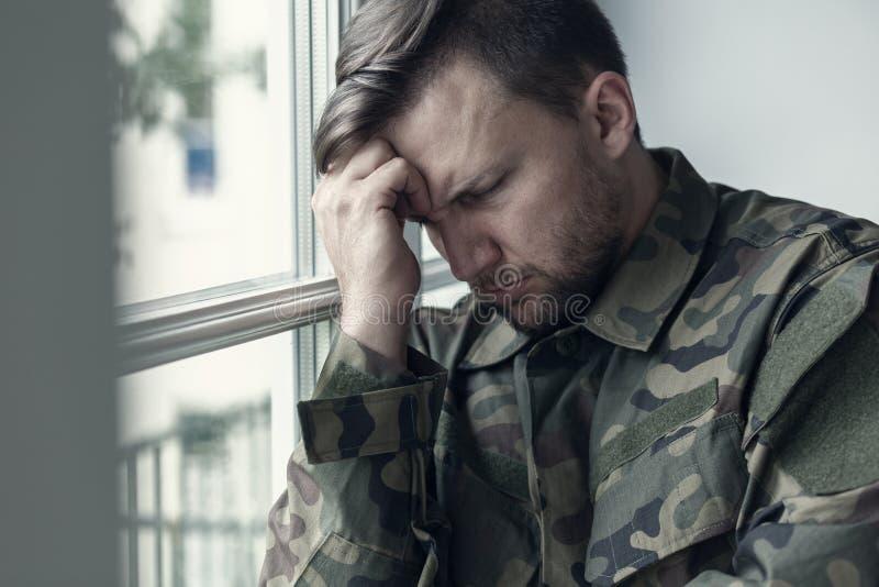 Подавленный и сиротливый солдат в военной форме с синдромом войны стоковые фото