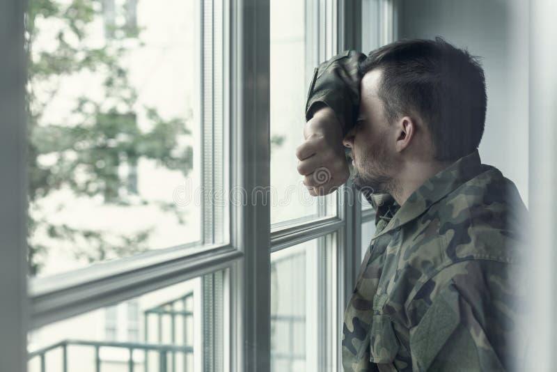 Подавленный и унылый солдат в зеленой форме с травмой после войны стоя около окна стоковые изображения