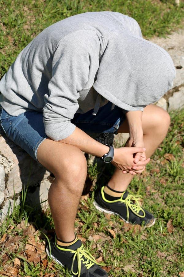 Подавленный мальчик с серыми фуфайкой и клобуком стоковые фото