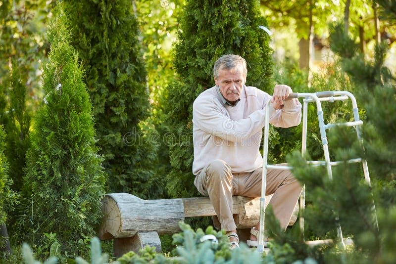 Подавленный старший человек с ходоком стоковое фото rf