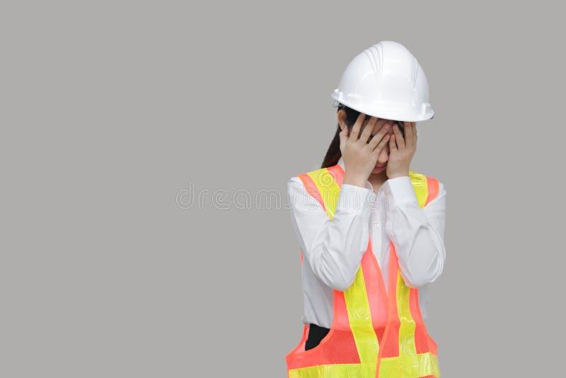 Подавленный усиленный молодой азиатский работник с руками на стороне плача на сером цвете изолировал предпосылку стоковое изображение rf