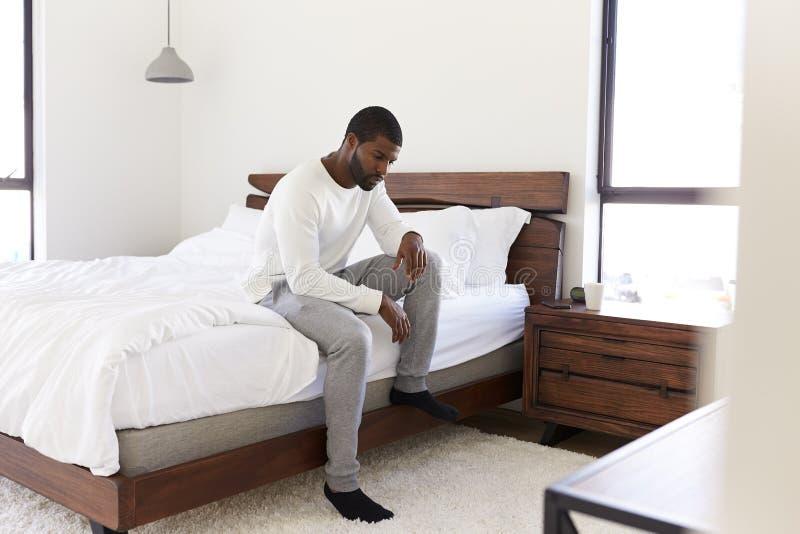 Подавленный человек выглядя несчастным усаживанием на стороне кровати дома стоковые фото