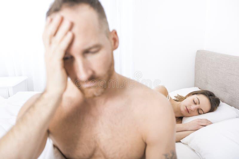 Подавленный человек сидя на краю кровати в спальне стоковые изображения