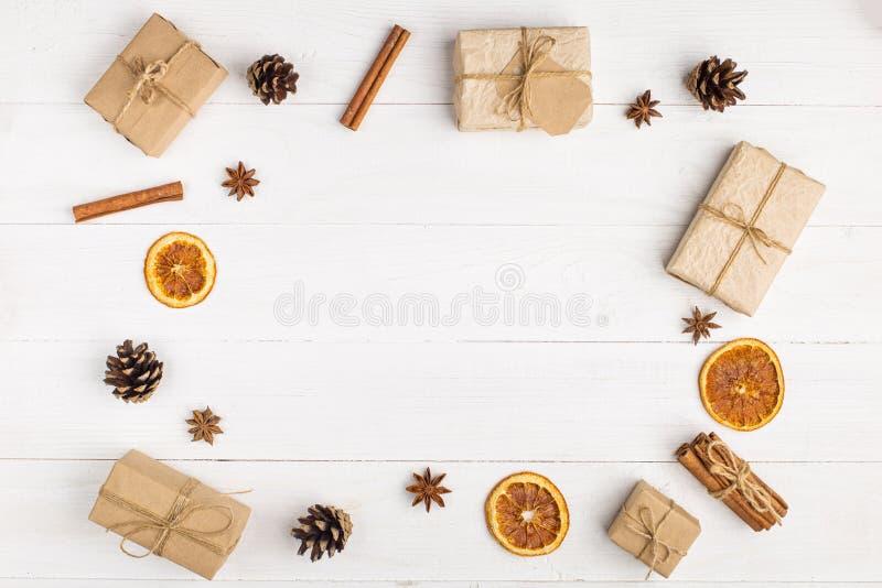 Подарки и специи Kraft бумажные на белой таблице Первоначальное оформление для рождества Красивый план, взгляд сверху, плоское по стоковое фото rf