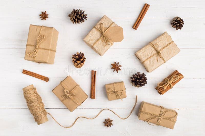 Подарки и специи Kraft бумажные на белой таблице Первоначальное оформление для рождества Красивый план, взгляд сверху, плоское по стоковое изображение rf