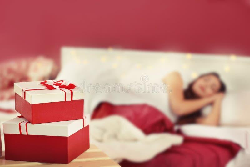 Подарки на рождество и запачканная спать женщина на предпосылке стоковые фото