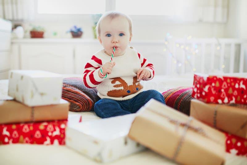 Подарки на рождество счастливого маленького ребенка раскрывая на ее очень первом рождестве стоковые изображения rf