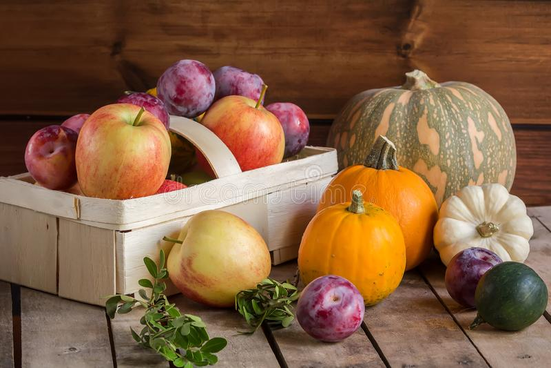 Подарки осени: яблоки и сливы в корзине и тыквах на деревянной предпосылке, составе осени, сборе стоковая фотография rf