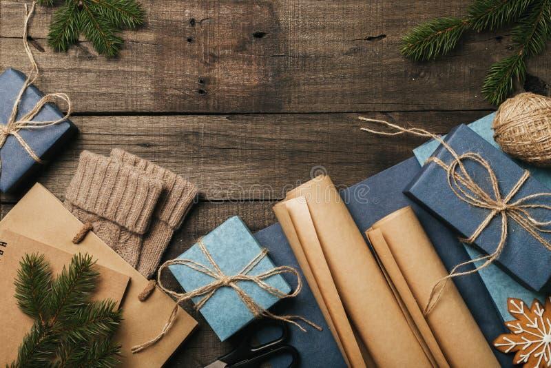 Подарки рождества упаковки в винтажной бежевой голубой бумаге крена на старом деревянном столе Взгляд сверху Плоское положение ск стоковые фотографии rf