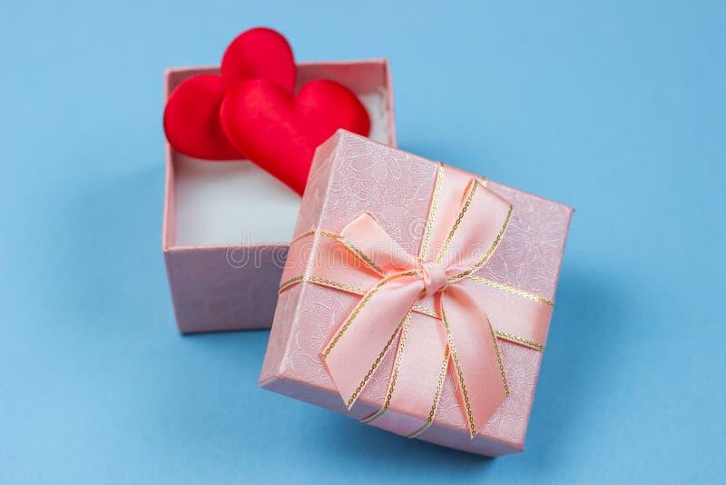 Подарок в красивой коробке и сердца красны и белы на голубой предпосылке стоковая фотография rf